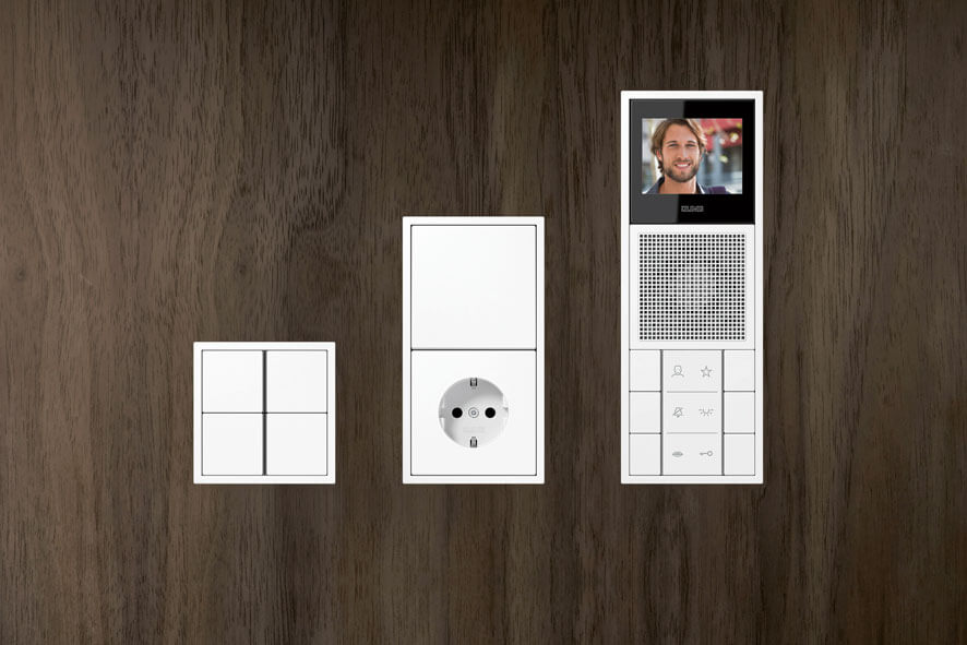 Tastsensoren LS-ZERO des Herstellers JUNG in 3 Variationen auf einer Holzwand
